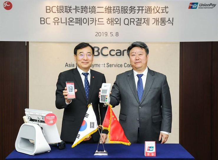 BC Card CEO Lee Mun-whan, left, and Union Pay International CEO Cai Jianbo show their joint QR application at BC Card's Seoul headquarters, Thursday. Courtesy of BC Card