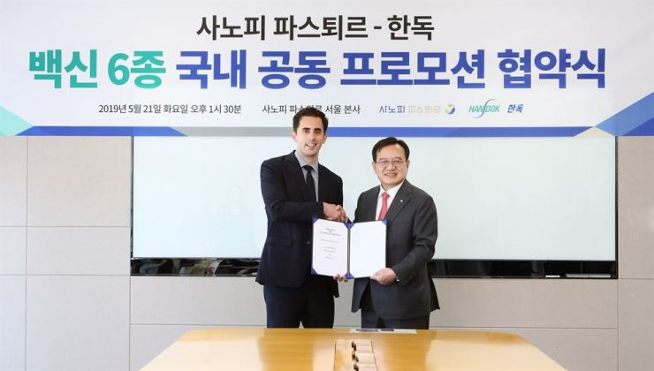 Sanofi Pasteur Korea General Manager Baptiste de Clarens, left, and Handok Chairman Kim Young-jin shake hands after signing an agreement on jointly promoting six vaccines in South Korea at the Seoul headquarters of Sanofi, Tuesday. Courtesy of Sanofi Pasteur