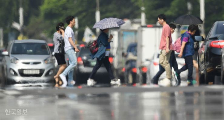 People cross the street at Yeouido, central Seoul, amid the first heat wave of the year, Friday. Temperatures hovered around 32 degrees Celsius on this day. / Korea Times photo by Bae Woo-han