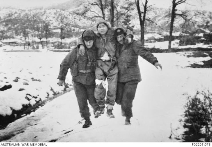 Two Australians carry an ROK soldier to safety. Tolkien wrote: 'I do not love the bright sword for its sharpness … nor the warrior for his glory. I love only that which they defend.' Photo from The Australian War Memorial Collection