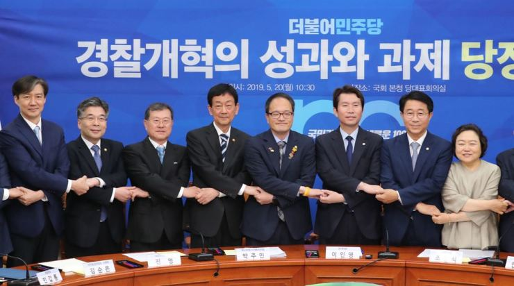 Representatives from Cheong Wa Dae, the government and the ruling Democratic Party of Korea hold hands during a trilateral meeting over police reform at the National Assembly in Seoul, Monday. / Yonhap