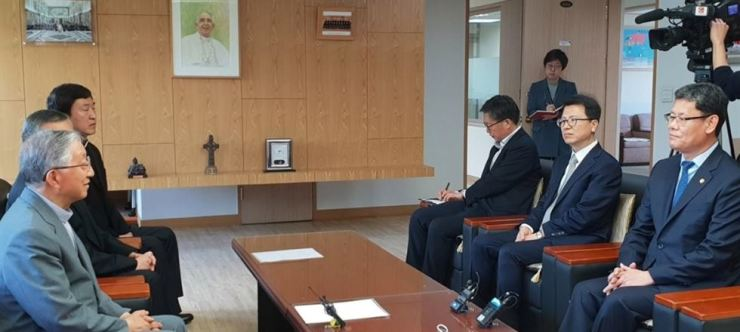 Unification Minister Kim Yeon-chul, right, speaks with Archbishop Hyginus Kim Hee-joong, left, chairman of the Catholic Bishops' Conference of Korea, in Seoul, Monday. Both sides exchanged their views on the government's plan to provide humanitarian food aid to North Korea. Yonhap