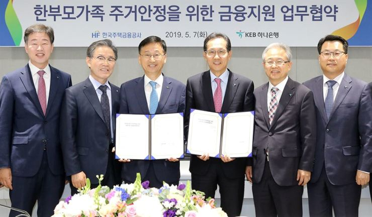 KEB Hana Bank CEO Ji Sung-kyoo, fourth from left, and Korea Housing Finance Corp. (KHFC) CEO Lee Jung-hwan, third from left, pose at the KHFC in Seoul, April 7, after signing an agreement to form a business alliance for helping single parents by offering financial support for their housing. Courtesy of KEB Hana Bank