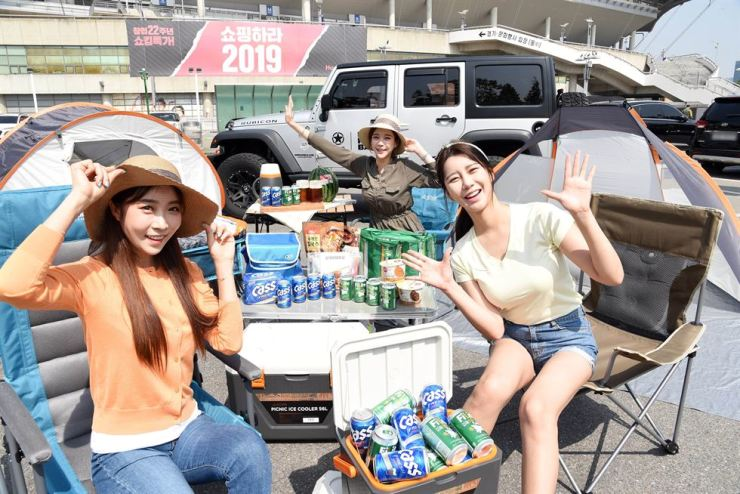 Models promote camping gear at a Homeplus branch in the Seoul World Cup Stadium in Mapo-gu, Thursday. The discount chain started sales for more than 90 camping items and goods for outdoor activities at discounted prices, and will provide vouchers to customers purchasing those items. Courtesy of Homeplus