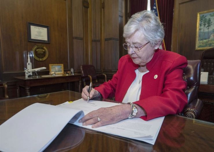 This photograph released by the state shows Alabama Gov. Kay Ivey signing a bill that virtually outlaws abortion in the state on May 15 in Montgomery, Ala. Republicans who support the measure hope challenges to the law will be used by conservative justices on the U.S. Supreme Court to overturn the Roe v. Wade decision which legalized abortion nationwide. AP