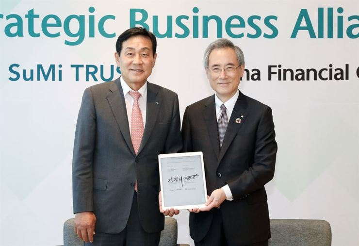 Hana Financial Group Chairman Kim Jung-tai, left, and Sumitomo Mitsui Trust Group President Tetsuo Ohkubo smile after agreeing to expand their ties at the Hana Global Campus in Incheon, Friday. Courtesy of Hana Financial Group