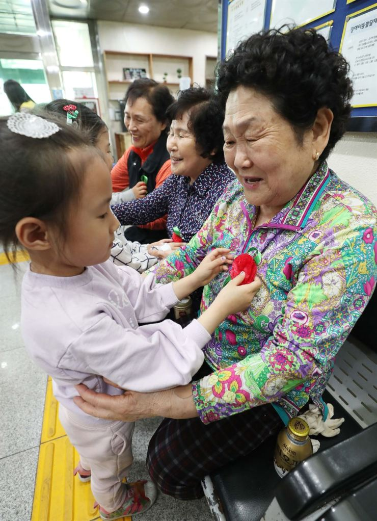 Children put paper carnations on elderly women at a social welfare center in Daegu, Wednesday, to celebrate Parents' Day. Children at Daegu Dalseo Elementary School and their parents prepared 800 paper carnations for the event. / Yonhap