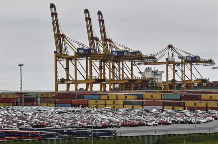 Cars for export and import are stored in front of containers on May 16 at the harbor in Bremerhaven, Germany, with 2 million vehicles per annum one of the largest automobile hubs in the world. AP