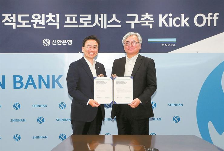 Joo Cheol-soo, left, vice president of Shinhan Bank's consumer protection group, poses with DNV GL Korea President Lee Jang-sup at the bank's headquarters in Seoul, May 17. The two sides agreed to collaborate in carrying out a so-called equator principle framework to assess and manage environmental and social risks before making financial decisions. Courtesy of Shinhan Bank