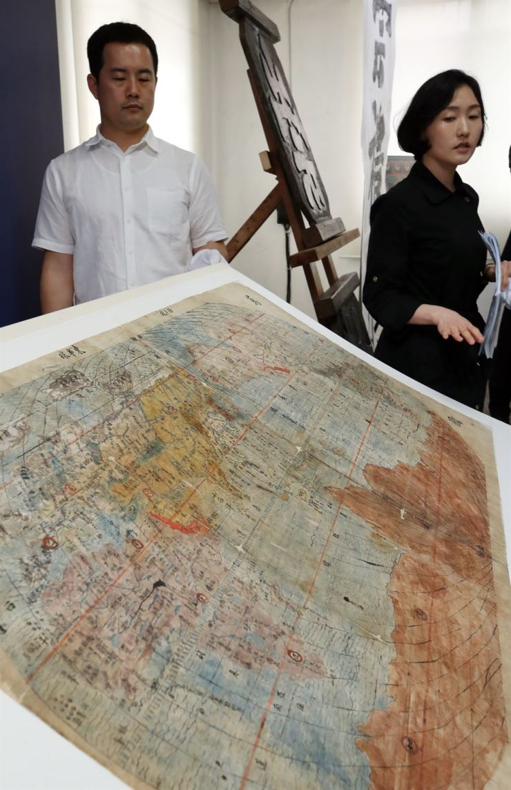 Police officers show Mankukjeondo, a world map from the 1392-1910 Joseon Kingdom that was found after being missing for 25 years, at Seoul Metropolitan Police Agency in Seoul, Tuesday. The police, in cooperation with the Culture Heritage Administration, caught two people for hiding 120 cultural assets including the map after obtaining them from thieves. / Yonhap