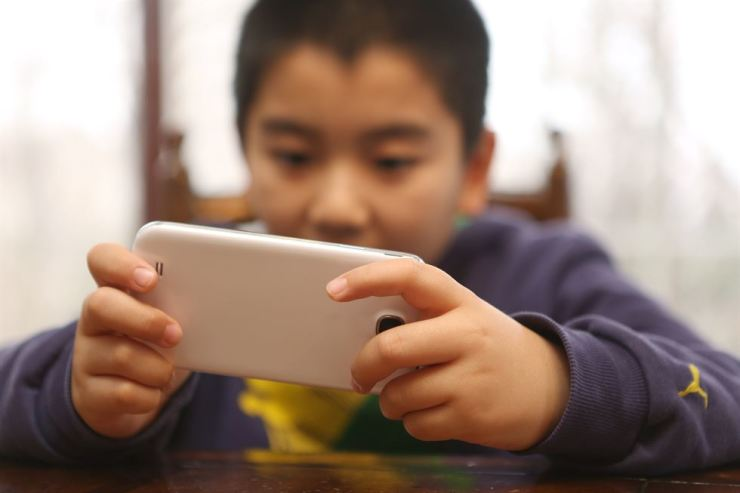 A boy plays a video game with his mobile phone. gettyimagesbank