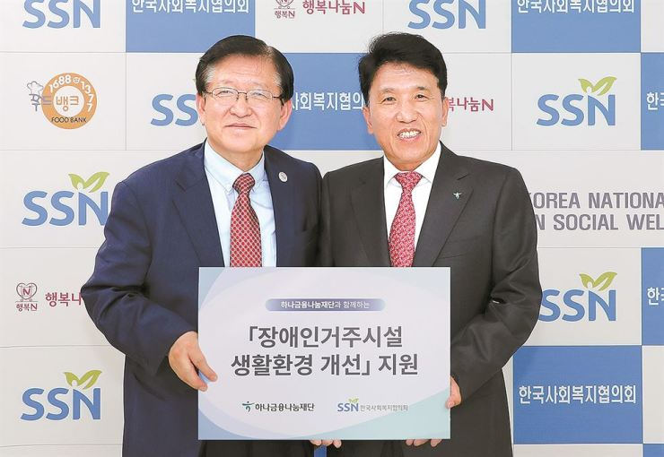 Hana Nanum Foundation Chairman Ham Young-joo, right, and Seo Sang-mok, head of the Korea National Council on Social Welfare (KNCSW) hold a sign promoting a corporate responsibility program at the KNCSW in Mapo, Seoul, May 17. The two entities agreed to give financial support to strengthen the infrastructure at living facilities for the disabled to help improve their mobility. Courtesy of Hana Nanum Foundation