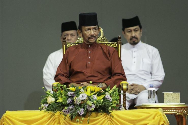 In this file photo taken on April 03, Brunei's Sultan Hassanal Bolkiah (C) attends an event in Bandar Seri Begawan. Brunei's sultan has announced that death by stoning for gay sex and adultery will not be enforced after a global backlash, but critics call for harsh sharia laws to be abandoned entirely. AFP