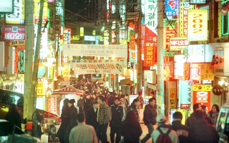 A street with small restaurants bustles with people in Sinchon, Seoul. Korea Times file