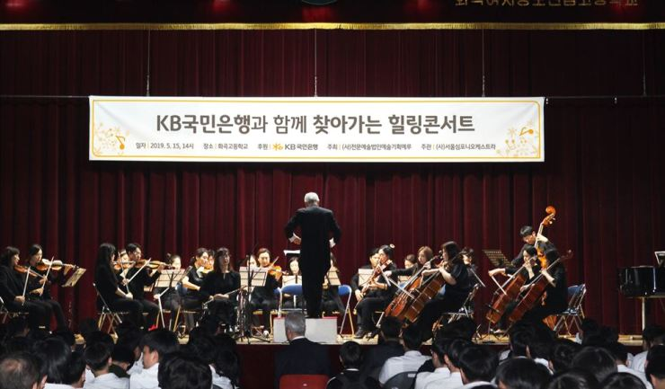 The Seoul Symphony Orchestra performs during a concert sponsored by KB Kookmin Bank at Hwagok High School in western Seoul, Wednesday. KB organized the event for teachers and students, to mark Teachers' Day. / Courtesy of KB Kookmin Bank