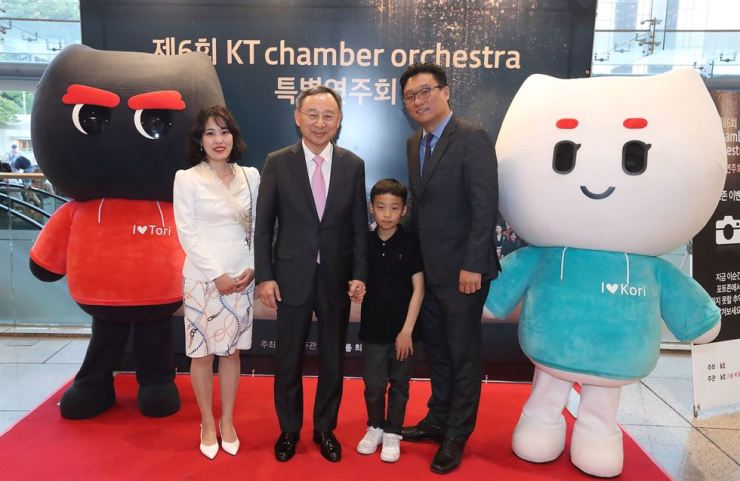 KT Chairman Hwang Chang-gyu, second from left, poses with an employee's family before a classical concert at the Seoul Arts Center, Thursday. The firm invited 2,400 employees and their families to the concert to express its gratitude to them following the launch of its fifth-generation (5G) network. / Courtesy of KT