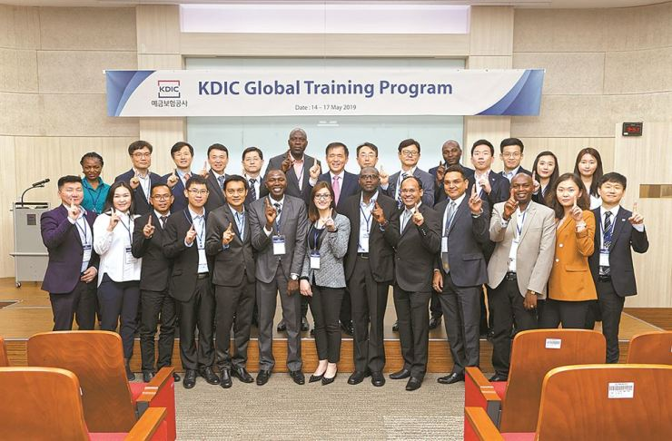 Korea Deposit Insurance Corp. (KDIC) CEO Wi Seong-bak, seventh from left in the back row, smiles with officials from eight countries at the KDIC headquarters in Seoul, May 14. The officials are attending a three-day training program organized by the KDIC. Courtesy of the KDIC