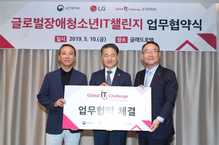 Health and Welfare Minister Park Neung-hoo, center, and LG Corp. Vice Chairman Kwon Young-soo, left, pose for a photo at a hotel in Seoul, Friday, after signing a business agreement for the successful hosting of the Global IT Challenge for Youth with Disabilities this year. The event is designed to enhance the information utilization skill of young people with disabilities to encourage their social participation. On the right is Kim In-kyu, president of the Korean Society for Rehabilitation of Persons with Disabilities. / Courtesy of Ministry of Health and Welfare