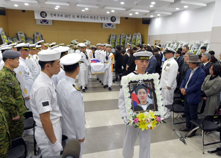 Sailors carry the portrait and coffin of the late Navy Petty Officer 1st Class Choe Jong-keun at a funeral ceremony at the Marine Medical Center in Jinhae, South Gyeongsang Province, Monday. Choe, 22, died in an accident on the Navy's destroyer Choi Young last Friday, when a mooring rope connecting the 4,400-ton ship to the dock in a Navy base in the southern port of Jinhae snapped, killing him and injuring four others. The accident happened during a welcoming ceremony for the destroyer returning home from its 193-day overseas deployment off the Somalia coast. Courtesy of Republic of Korea Navy