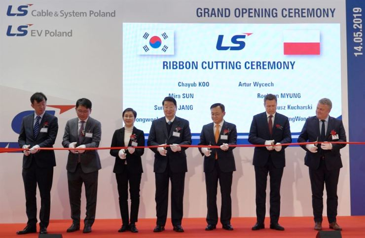 LS Cable & System Chairman Koo Cha-yub, center, cuts a ribbon while celebrating the opening of the firm's cable and battery components manufacturing plant in Dzierzoniow, Poland, Tuesday, with local government officials. / Courtesy of LS Cable & System