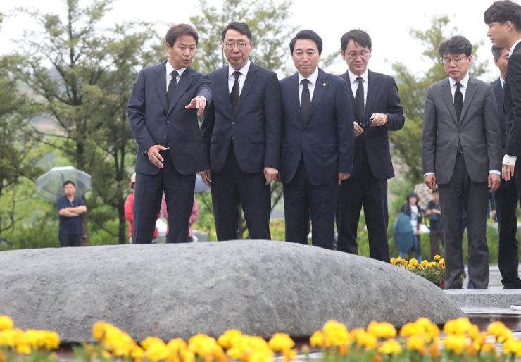 Im Jong-seok, left, former presidential chief of staff, talks in front of the grave of the late President Roh Moo-hyun, along with his former colleagues in Gimhae, South Gyeongsang Province, Saturday. They paid a visit to the late president's grave in a move to commemorate the 39th anniversary of the Gwangju Uprising, a pro-democracy movement. From left are Im, former senior presidential press secretary Yoon Young-chan, former presidential spokesman Park Soo-hyun and former chief of the presidential press center Kwon hyuk-ki. Yonhap
