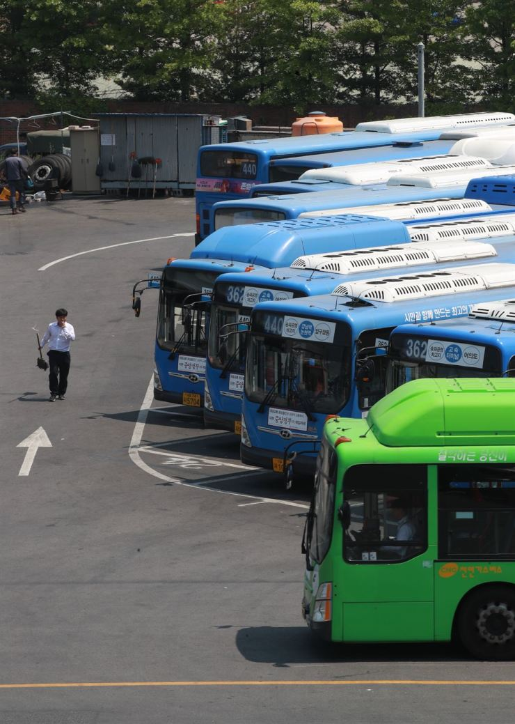Buses are parked at a bus parking lot in Songpa-gu, eastern Seoul, Tuesday, a day ahead of a planned strike by 35,000 unionized bus drivers across the country. The drivers are calling for countermeasures against an expected salary cut along with the implementation of the 52-hour workweek system in July. Bus drivers in Daegu and Incheon reached an agreement with their companies and called off the strike plan, while those in other regions have not as of 5 p.m. / Yonhap