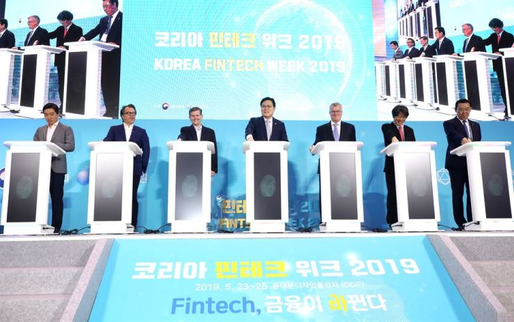 Financial Services Commission Chairman Choi Jong-ku, center, takes part in an opening ceremony for Korea Fintech Week 2019 with other dignitaries at the Dongdaemun Design Plaza in Seoul, Thursday. Second from left are Visa's Global Head of Strategic Partnerships and Venture Matt Dill, Ant Financial's Senior Vice President of Global Business Douglas Feagin, Chairman Choi and U.K. Ambassador to South Korea Simon Smith. / Yonhap