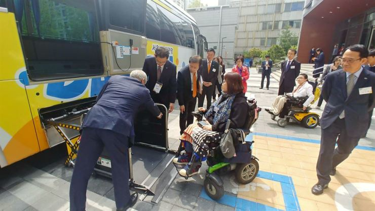 Seoul Metropolitan Government officials help a disabled citizen board a Danurim tour bus, a special bus equipped with a wheelchair lift, in central Seoul, Tuesday, after the opening ceremony of Danurim Tour Center dedicated to supporting travel by the disabled and the elderly. Courtesy of Danurim Tour Center