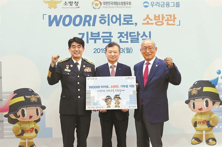 Woori Bank Customer Brand Group head Cho Soo-hyung, center, holds a promotional banner with National Fire Agency policy division director Choi Byeong-il, left, at the commercial bank's head branch in Jung-gu, central Seoul, Monday. Woori said it will hold various events to support the nation's firefighters and their families. / Courtesy of Woori Financial Group
