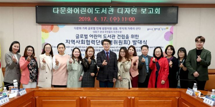 Chong Won-o, center, head of Seongdong-gu Office, poses in the office building, April 17, with members of the operation committee for a new multilingual children's library, including eight foreign mothers from multicultural families. / Courtesy of Seongdong-gu Office