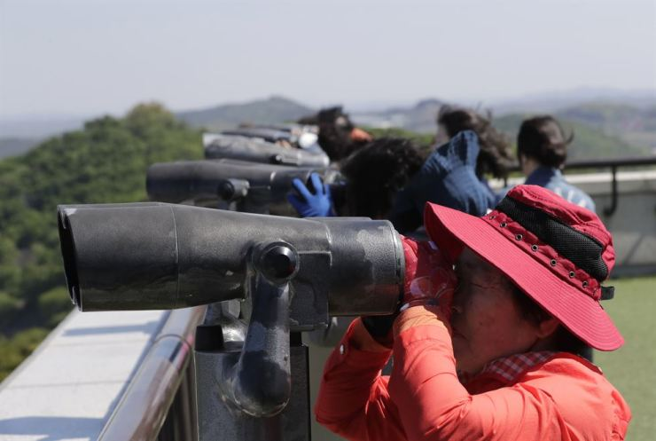 Visitors use binoculars to see the North side from the unification observatory in Paju, South Korea, May 6. North Korea appears to have tested a new short-range missile. AP-Yonhap