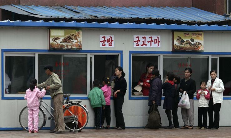 People wait in line in front of a food stand in the North Korean capital of Pyongyang early morning Oct. 11, 2010. Reuters-Yonhap