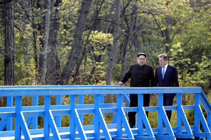 President Moon Jae-in, right, and North Korea's leader Kim Jong-un take a stroll at the Foot Bridge on the South Korean side of the truce village at Panmunjeom in the border area, during their first summit on April 27, 2018. Korea Times file