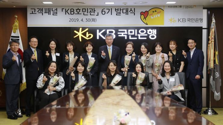 KB Kookmin Bank CEO Hur Yin, second row sixth from left, makes a finger heart gesture with members of the customer review panel and bank officials at the bank's headquarters on Yeouido in Seoul, April 30. Courtesy of KB Kookmin Bank