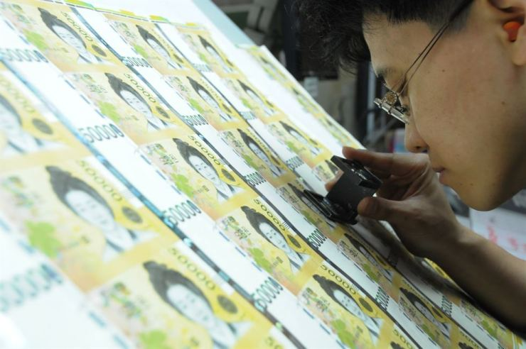 An employee at the Korea Minting, Security Printing and ID Card Operating Corp. inspects the graphic template for 50,000-won banknotes. Courtesy of Korea Minting, Security Printing and ID Card Operating Corp.