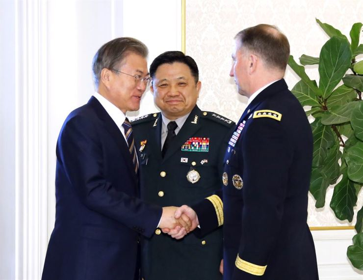 President Moon Jae-in shakes hands with USFK chief Gen. Robert Abrams, right, at the start of his luncheon with commanders of the USFK and the South Korean military at Cheong Wa Dae, Tuesday. Behind Moon is Republic of Korea Joint Chiefs of Staff Chairman Gen. Park Han-ki. Yonhap