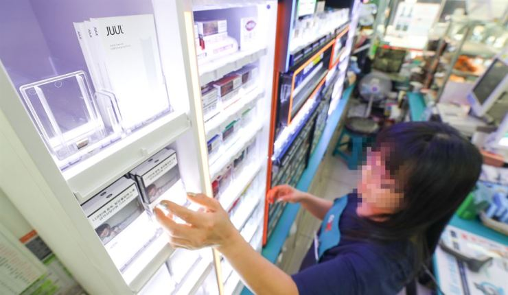 An employee arranges JUUL products at a convenience store in Yongsan, Seoul, Friday. / Yonhap