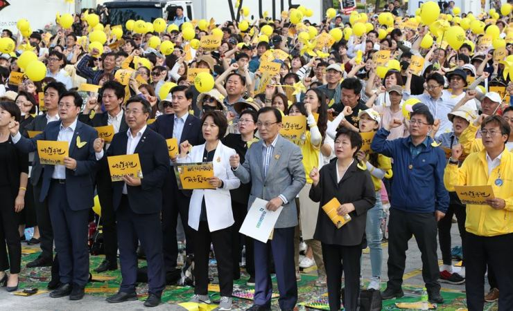 Ruling DPK party leader Lee Hae-chan, center in the front row, and senior party officials sing a song on the sidelines of their participation in an event in downtown Seoul, May 18. to commemorate the death of the late President Roh Moo-hyun. Korea Times file