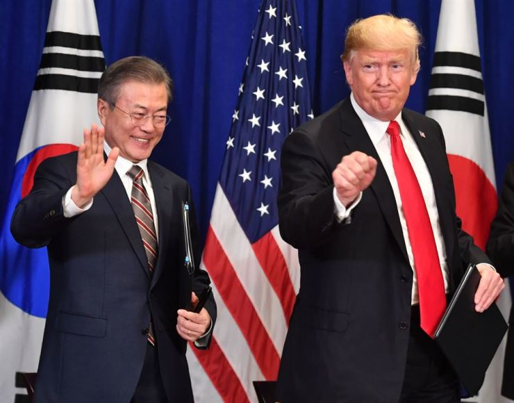 In this file photo taken on Sept. 24, 2018, U.S. President Donald Trump and President Moon Jae-in gesture after signing a trade agreement at a bilateral meeting in New York, a day before the start of the General Debate of the 73rd session of the General Assembly. Trump will visit South Korea next month to meet Moon over their efforts to persuade North Korea to scrap its nuclear weapons arsenal. AFP-Yonhap