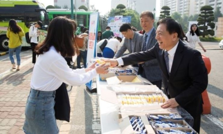 Pai Chai University President Kim Seon-jae, right, smiles while giving away sandwiches to students inside the university campus in Daejeon, about 140 kilometers south of Seoul, Tuesday, a day before Teacher's Day. Courtesy of Pai Chai University