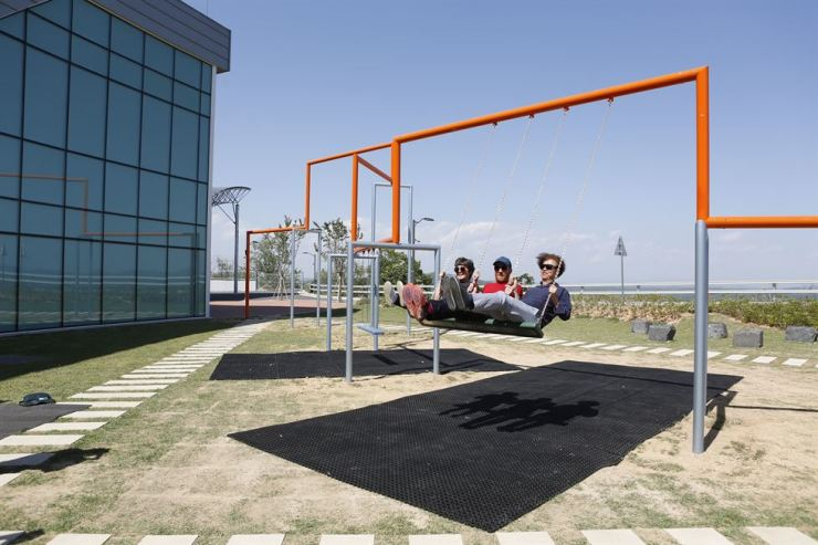 From left, Kim Sun-jung, artistic director of the Real DMZ Project, Jakob Fenger of Superflex and Zoh Kyung-jin, a landscape design theory professor at Seoul National University, ride Superflex's installation 'One Two Three Swing!' Tuesday at Dora Observatory in Paju, Gyeonggi Province, which looks across the Demilitarized Zone into North Korea. Courtesy of Real DMZ Project