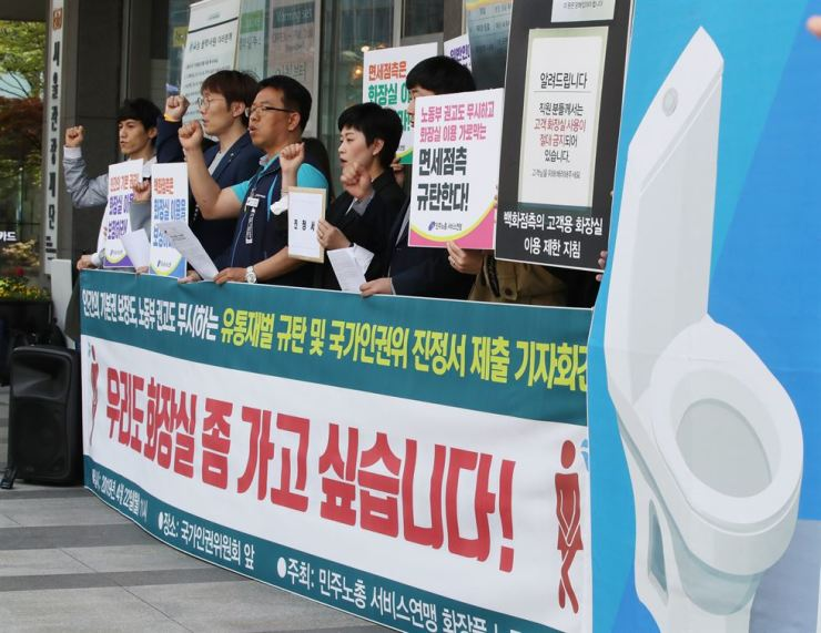 Members of the Korean Federation of Service Workers' Unions rally in front of the National Human Rights Commission building in downtown Seoul, April 22, to condemn the restriction on the use of customer restrooms. Yonhap