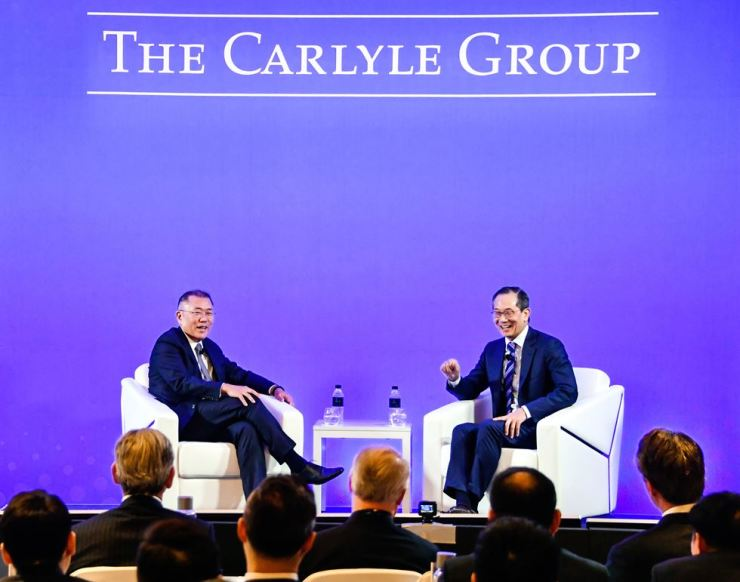 Hyundai Motor's Executive Vice Chairman Chung Eui-sun, left, and Lee Kew-song, co-chief executive of The Carlyle Group, chat at an event hosted by The Carlyle Group in Seoul, Wednesday. / Courtesy of Hyundai Motor Group