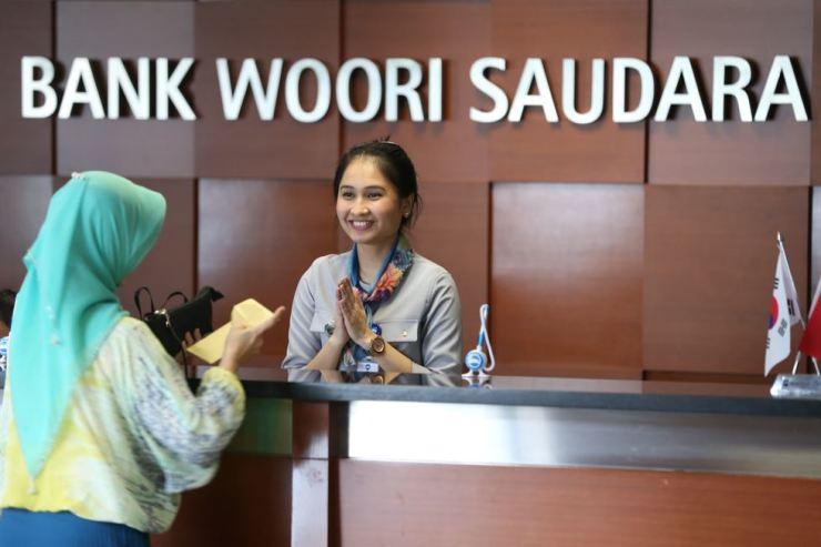 A Bank Woori Saudara employee greets a customer in Jakarta, Indonesia in this 2018 file photo. Courtesy of Woori Bank