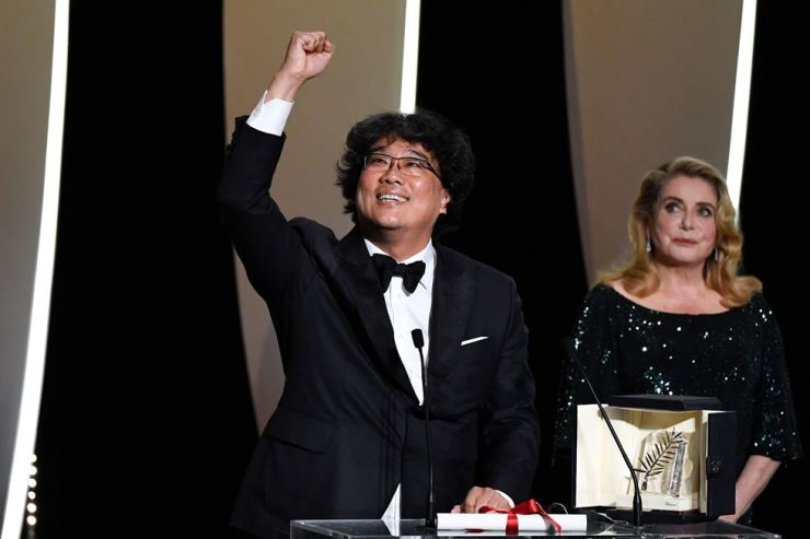 South Korean director Bong Joon-Ho (L) reacts on stage next to French actress Catherine Deneuve after he was awarded with the Palme d'Or for the film 'Parasite (Gisaengchung)' on May 25, 2019 during the closing ceremony of the 72nd edition of the Cannes Film Festival in Cannes, southern France. (Photo by CHRISTOPHE SIMON / AFP)