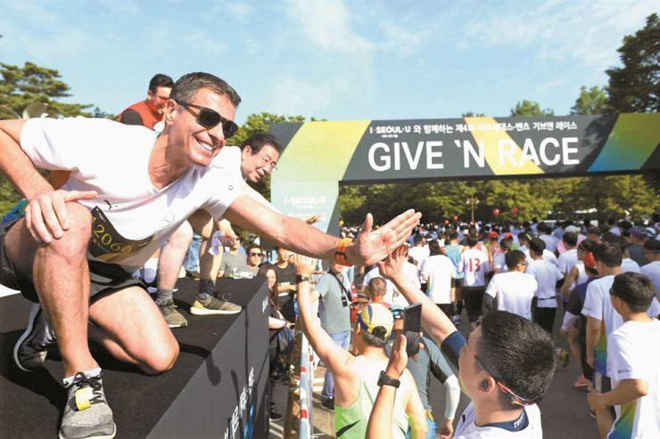 Mercedes-Benz CSR Committee Chairman Dimitris Psillakis, left, and Seoul Mayor Park Won-soon, second from left, cheer on runners in the 'GIVE 'N RACE' hosted by the car company. This year's marathon was the largest, with about 20,000 participants. Courtesy of Mercedes-Benz Korea