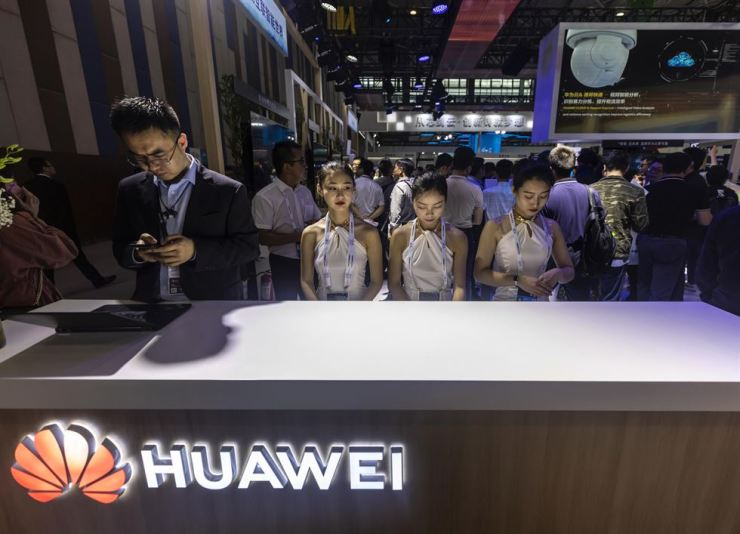 Employees stand at the Huawei booth during Big Data Expo in Guiyang, Guizhou province, China, May 26. EPA