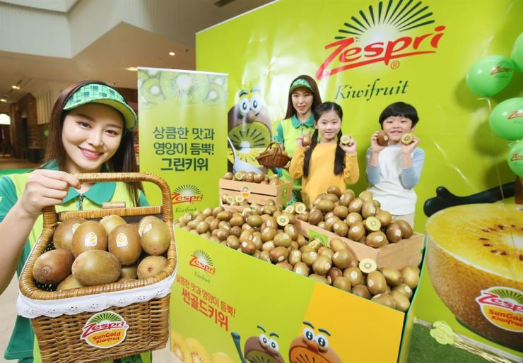 Models pose with Zespri kiwis at Starfield shopping mall in Goyang, Gyeonggi Province, Friday. A Zespri International Korea official said the company is giving away gifts to customers who buy the kiwi product at the shopping mall for three days from May 10. / Courtesy of Zespri