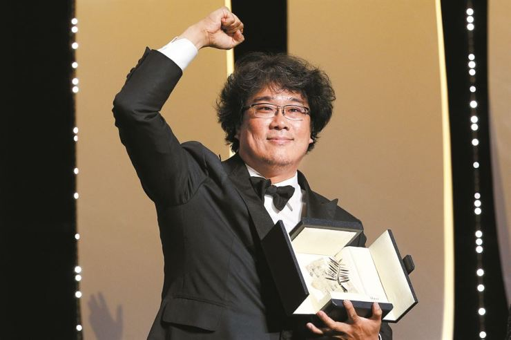 Director Bong Joon-ho, holding Cannes Palme d'Or award, reacts after winning the top prize for his latest film 'Parasite' during the closing ceremony of the 72nd Cannes Film Festival in southern France, Saturday night. The director became the first Korean director to bring home the top prize at the world's most prestigious film festival. / Courtesy of Reuters-Yonhap