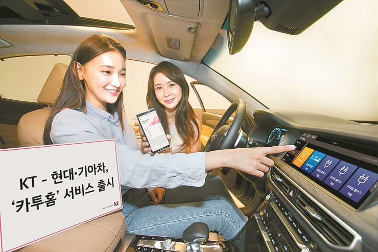 Models in a Kia Motors K7 sedan demonstrate KT's Car to Home, an in-vehicle connected device control service, in this photo provided by the mobile carrier, Wednesday. / Courtesy of KT